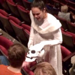 A ghostly cast member from 'A Christmas Carol' explains her costume to a Sensory Friendly performance guest.